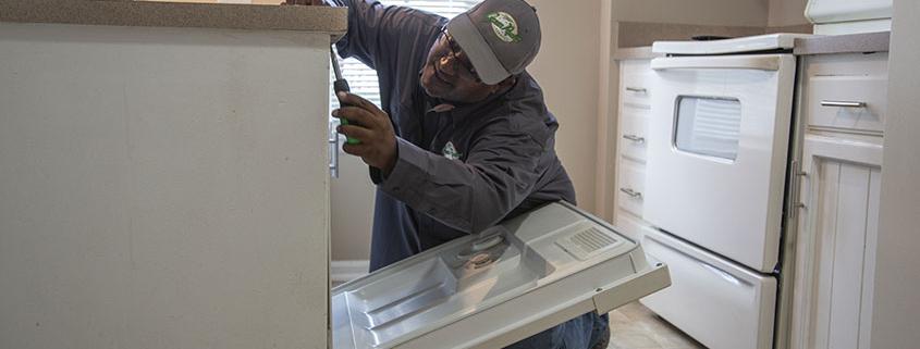 Worker repairing a dishwasher
