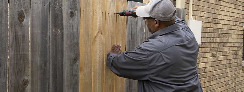 Worker fixing a fence