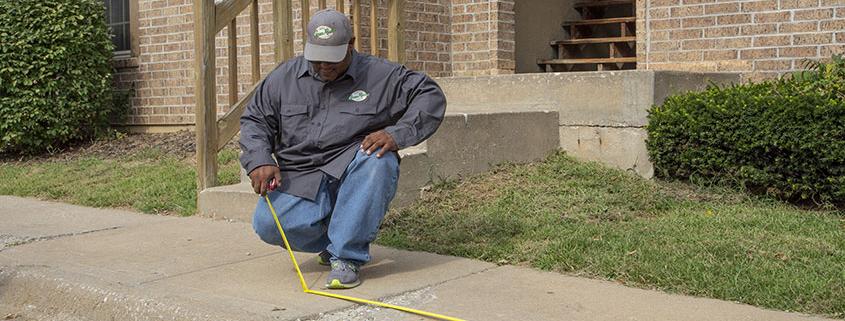 Worker measuring a sidewalk for repairs