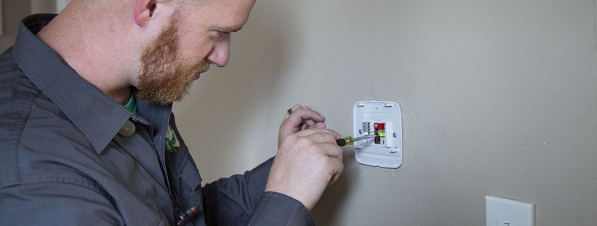 Worker fixing a thermostat